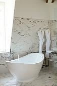 Modern light marble bathroom and ceramic bath near window