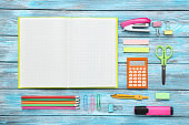 School supplies with blank sheet of paper on blue wooden table