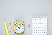 Calendar page with alarm clock and pen on gray background
