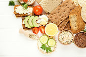 Crispbread with cream cheese, eggs and vegetables on white wooden table
