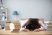 Woman lying on table with books at home.