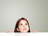 Cute little child girl looking up on the desk at school.