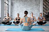 Women group exercising and sitting in yoga lotus position indoors.