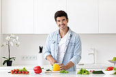 Young man cutting vegetables for salad at table in modern light kitchen.