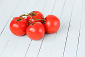 Red tomatoes on a branch on a wooden table.