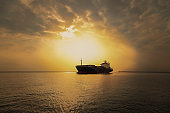 International Container Cargo ship in the ocean, Freight Transportation, Nautical Vessel at sunset.