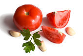 red tomato in the section macro photography on a white background with parsley and garlic