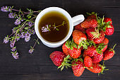 green tea with thyme and lots of red strawberries on a wooden background