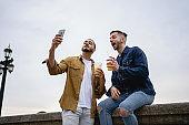 Bonding homosexual couple doing selfies while having fun