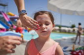 Mother applying sunscreen protection lotion on her daughter face