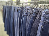 stylish denim trousers in a clothing store on display stands