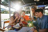 Cheerful group of students having fun time at a cafe