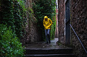Male tourist in raincoat trying to find a place to hide from rain