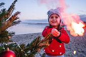 Playful carefree girl holding sparkler and celebrating Christmas Eve on the beach