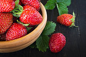 a full Cup of red juicy strawberries on a black wooden background with foliage