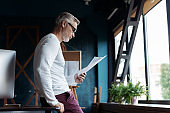 Casual Grey-haired Mature man reading paper in his office.