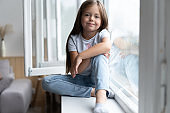 Beautiful little girl watching out the window. Young girl looking from window. Cheerful kid lies at windowsill