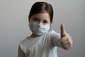 Little girl wearing mask for protect and thumb up gesture for stop corona virus outbreak.