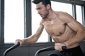 Man using exercise bike at the gym. Fitness male using air bike for cardio workout at Functional training gym