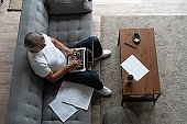 Middle-aged man working from home-office on laptop.
