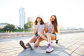 Two Young Woman sitting on Skateboard Happy Smiling. Playful Friends Enjoy Sunny day. Outdoor Urban. Beautiful Model Girl in Fashion Trendy Outfit