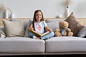 Young girl reading book at home. Distance education, home education. Self isolation concept.