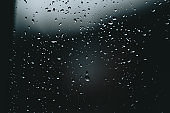 Horizontal background of some moody rain drops over a window with dark tones and textured droplets