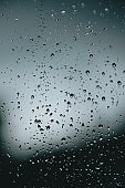 Vertical background of some moody rain drops over a window with dark tones and textured droplets