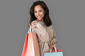 Shopping Concept. Woman standing isolated on grey with bags smiling cheerful