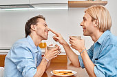 Two young adult homosexual man having fun at breakfast