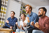 Men watching sport on tv together at home shouting happy