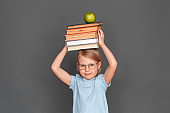 Freestyle. Little girl in eyeglasses isolated on grey with books and apple above the head smiling joyful