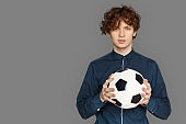 Sporty Lifestyle. Teenager boy standing isolated on grey with soccer ball smiling playful space for text or product