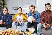 Men watching sport on tv together at home holding ball