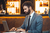 Businessman sitting in a business center bar using laptop serious