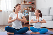 Two persons adult beauty women and little charming girl doing yoga pilates exercise fitness. Calm inspired balance harmony concept. Sits on floor mat, legs bent in lotus position at home background.