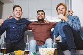 Men watching sport on tv together at home togetherness
