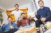 Men watching sport on tv together at home excited