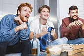 Men watching sport on tv together at home boxing