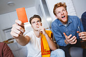 Men watching sport on tv together at home red card