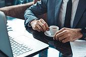 Businessman sitting in a business center restaurant srinking espresso close-up