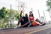 Outdoors Activity. African couple sitting on basketball court taking selfie on smartphone posing to camera cheerful