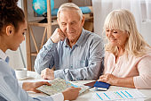 Travel agent at office sitting with senior clients choosing destination on map happy