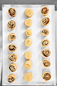 Raw cinnamon rolls and delicious pastry dessert on tray