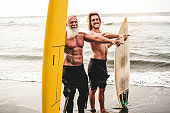 Multigeneration friends going to surf on tropical beach - Family people having fun doing extreme sport - Joyful elderly and healthy lifestyle concept - Focus on senior face