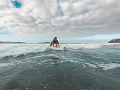 Fit female athlete surfing at sunset - Surfer woman performing outdoor inside ocean - Extreme sport, travel, healthy lifestyle, adventure and vacation concept - Focus on her body