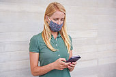 Young woman using mobile phone while wearing face mask during coronavirus outbreak - Female person watching videos on smartphone - Covid 19 lifestyle - Focus on eyes