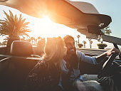 Happy people having fun in convertible car in summer vacation at sunset - Young couple enjoyng  holiday on cabrio auto outdoor - Travel, youth lifestyle and wanderlust concept - Soft focus on man face