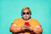 Curvy woman using smartphone outdoor - Young female having fun listening music playlist on mobile phone while wearing face protective mask - Coronavirus lifestyle concept