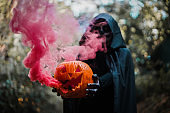 Girl with halloween costume and make up, holding a pumpkin with a smoke bomb inside - Holidays, party, scary and autumn concept - Focus on butternut